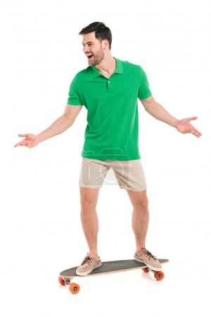 cheerful young man in shorts and polo shirt standing on skateboard isolated on white