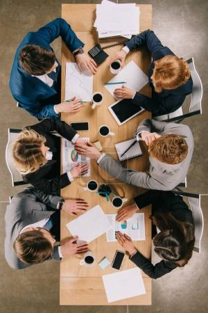 Top view of businesspeople discussing at table with digital devices, coffee cups and documents