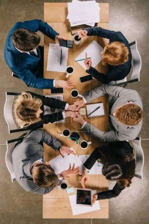 Top view of business partners working at table with coffee, documents and gadgets in office
