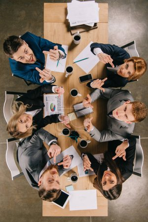 Top view of business colleagues showing middle fingers and sitting at table in office