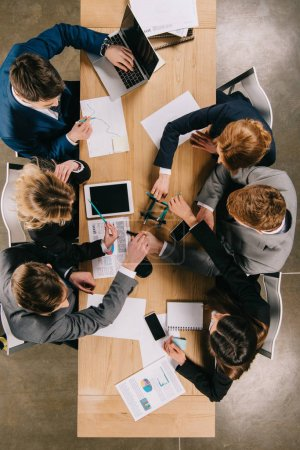 Photo for Overhead view of business partners doing construction with pencils at table in office - Royalty Free Image