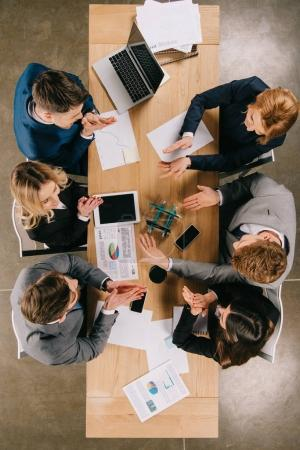 Top view of business colleagues doing construction with pencils at table in office