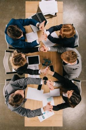 Top view of businesspeople holding hands of each other while sitting at table in office