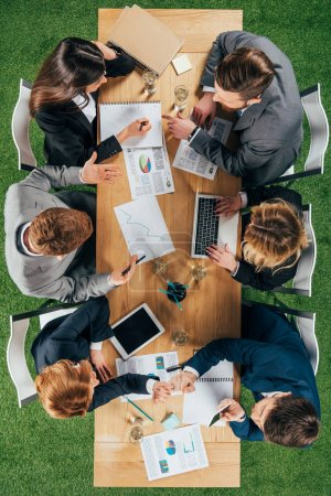 overhead view of business colleagues having discussion at table with documents and devices in office