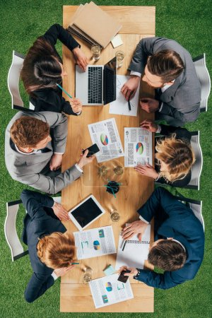 overhead view of business partners having discussion at table with documents and devices in office