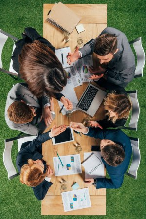 overhead view of angry business partners having discussion at table with documents and devices in office