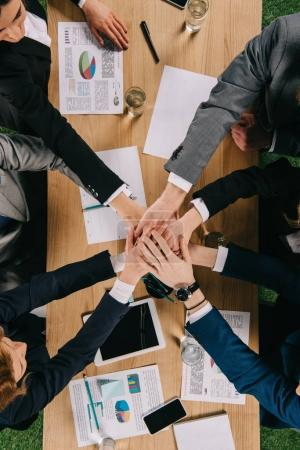 Photo pour Cropped view of business partners at table in office, businessesspeople team work collaboration relation concept - image libre de droit