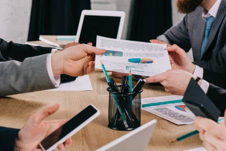 Photo for Cropped view of businessman giving diagram to partner while business colleagues working at table in office - Royalty Free Image