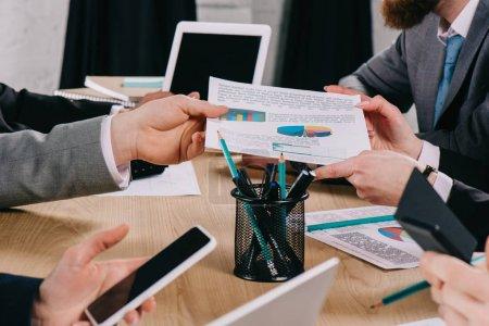 Photo pour Vue recadrée de l'homme d'affaires donnant le diagramme au partenaire tandis que les collègues d'affaires travaillant à la table dans le bureau - image libre de droit