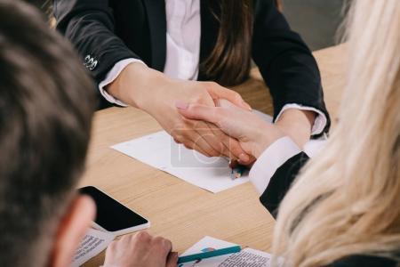 Photo pour Vue recadrée de deux femmes d'affaires serrant la main à table au bureau - image libre de droit
