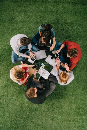 Top view of businesspeople working with devices and documents on grass