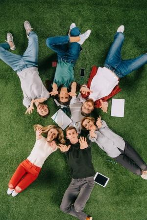overhead view of happy businesspeople with arms up laying on grass