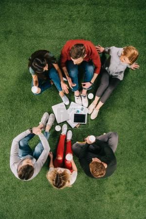 Vue de dessus des collègues de travail avec café discuter sur l'herbe