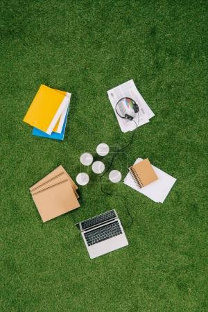 Photo for Top view of business objects and office supplies laying on green grass carpet - Royalty Free Image