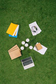 Top view of business objects and office supplies laying on green grass carpet