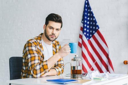 Jeune homme d'affaires travaillant par ordinateur portable et de boire du café
