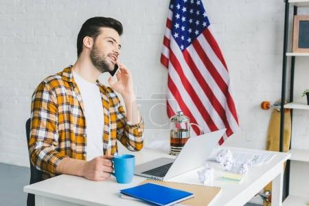 Young freelancer drinking tea and talking on smartphone in light office