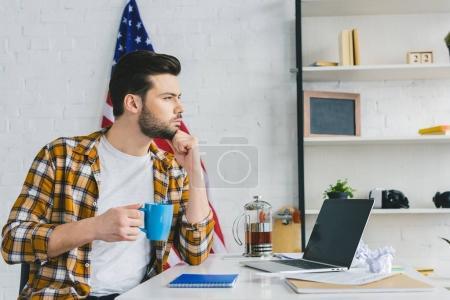Homme pensif, boire du café à la table de travail à domicile
