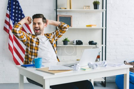 Tired businessman stretching by working table at home office