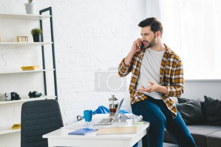 Young man sitting on table and talking on phone in light office