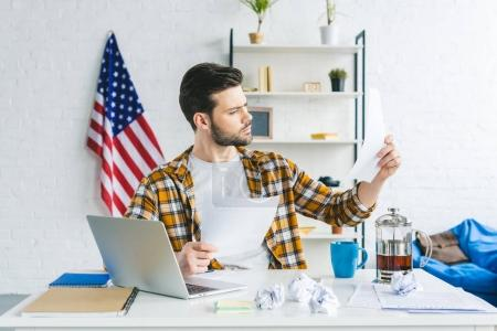 Businessman studying papers while working by laptop at home office