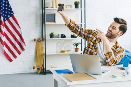 Photo for Smiling man taking selfie at home office - Royalty Free Image