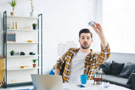 Man throwing crumpled paper while working at home office