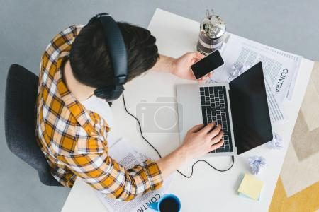 Young freelancer working by laptop and holding smartphone at home office
