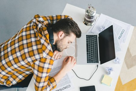 Man sleeping on table with laptop at home office