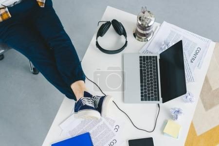 Closeup view of male feet on table with laptop in light office