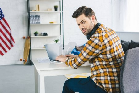 Freelancer working by laptop at home office