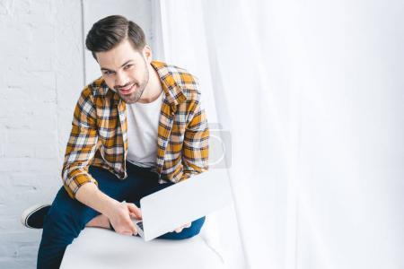 Bearded man holding laptop and sitting on windowsill