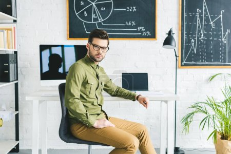 Serious man sitting by table with computers in light office