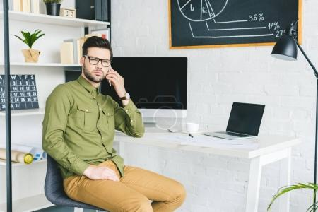 Freelancer working by computer and talking on phone in light office
