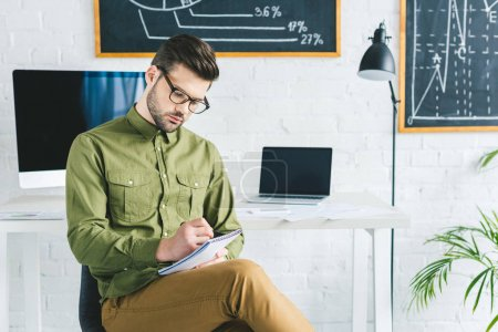 Thoughtful businessman taking notes by working table in light office
