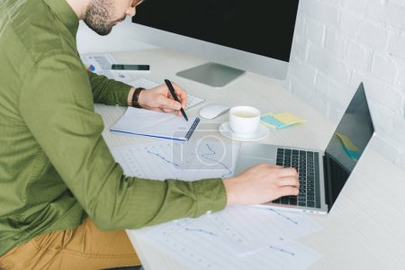 Young man working by computer and taking notes at home office