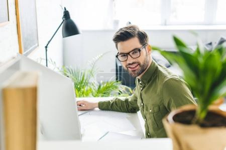 Photo pour Homme souriant assis à table avec ordinateur au bureau à la maison - image libre de droit