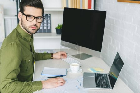 Man in glasses working by table with computer and laptop at home office