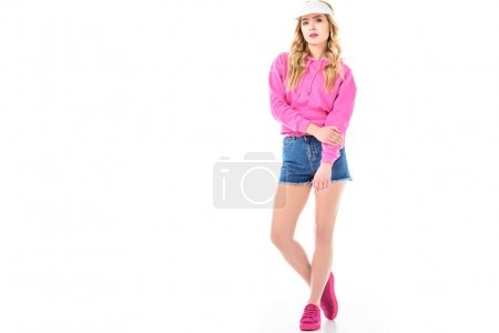 Attractive young woman dressed in pink and wearing tennis cap isolated on white