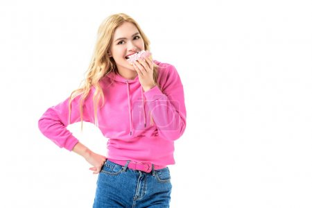 Attractive young girl dressed in pink biting doughnut isolated on white