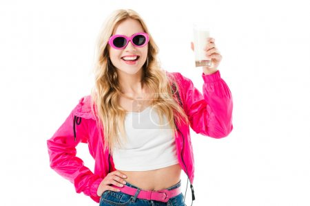 Attractive young woman dressed in pink holding glass of milk isolated on white