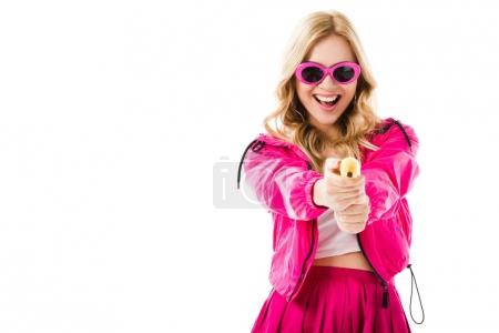 Blonde woman in pink clothes holding banana like gun isolated on white