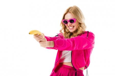 Young girl wearing pink shooting from banana isolated on white