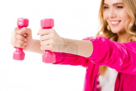 Pink dumbbells in hands of young girl isolated on white