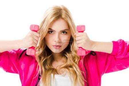 Blonde woman in pink clothes holding dumbbells isolated on white