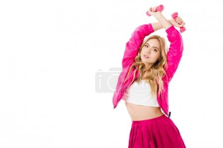 Attractive young woman dressed in pink exercising with dumbbells isolated on white