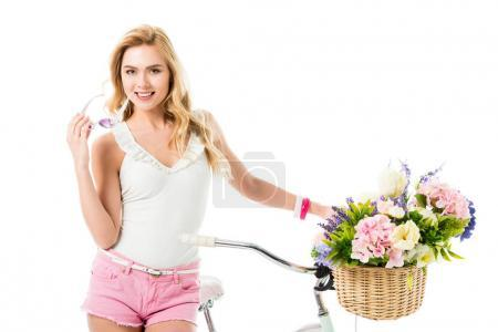 Attractive young woman standing by bicycle with flowers in basket isolated on white