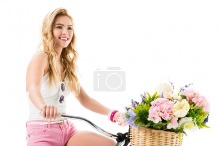Photo for Blonde happy girl riding bicycle with flowers in basket isolated on white - Royalty Free Image