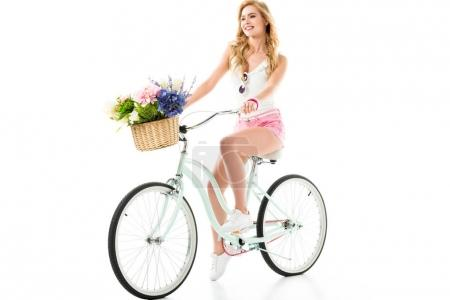 Young smiling girl riding bicycle with flowers in basket isolated on white
