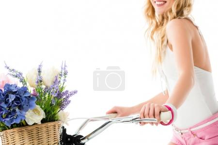 Young girl riding bicycle with flowers in basket isolated on white